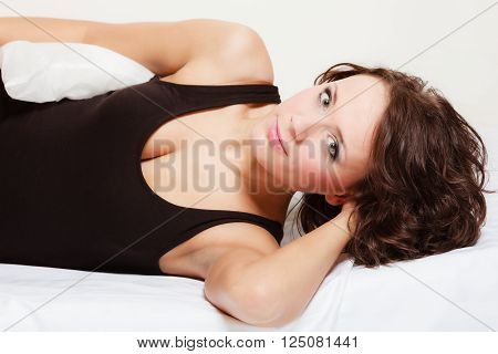 Sexy lazy girl in black body lying with pillow on the bed. Young attractive woman relaxing lazing in bedroom at morning.