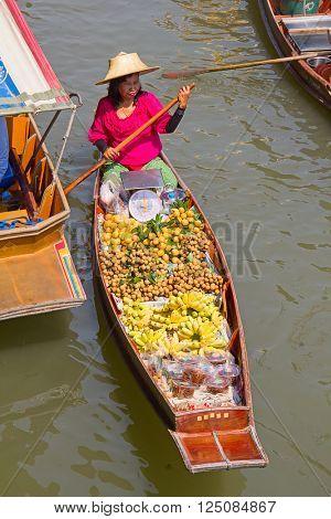 RATCHABURI, THAILAND - FEB 20: A woman serves Thai food at Damnoen Saduak floating market on February 20, 2011 in Ratchaburi, Thailand. The local market is popular for traditional food and souveniers.