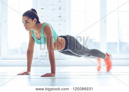 Working her core muscles. Full length of young beautiful woman in sportswear doing plank while standing in front of window at gym