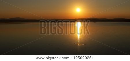 Summer silhouette panoramic landscape - the sun setting behind the mountains on Elovoe Lake or Spruce Lake in Southern Urals Russia poster