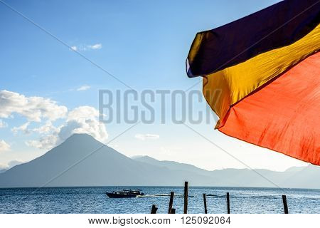 Colorful umbrella & San Pedro volcano in evening light at Lake Atitlan in Guatemalan highlands.