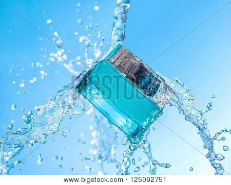 The blue  jar of moisturizing cream with big water splash around the jar  on the blue gradient background ** Note: Visible grain at 100%, best at smaller sizes