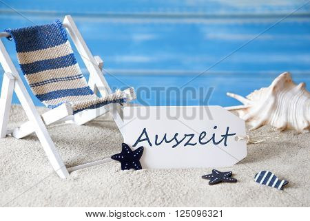 Summer Label With German Text Auszeit Means Downtime. Blue Wooden Background. Card With Holiday Greetings. Beach Vacation Symbolized By Sand, Deck Chair And Shell.