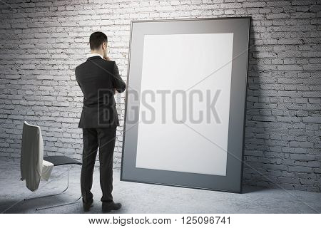 Blank frame leaning on brick wall with thoughtful businessman staring at it. Mock up 3D Render