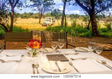 A safari game drive vehicle is parked close to a breakfast setting in the African bush. Tourists are treated to a bush breakfast after game viewing in the Cradle of Humankind South Africa.