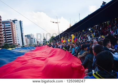 Quito, Ecuador - April 7, 2016: Group of people displaying a very big Ecuadorian Flag, protest signs, and journalists during anti government protests in Shyris Avenue