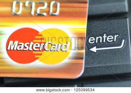 GDANSK, POLAND - JANUARY 18, 2016: Closeup of MasterCard debit card on laptop keyboard. MasterCard Incorporated is American multinational financial services corporation. It was founded in 1966.
