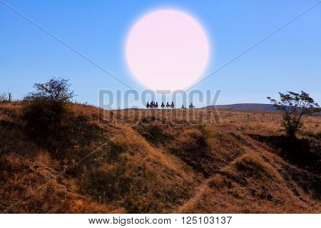 group of riders on the hill with big moon