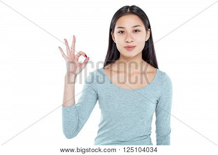 Studio shot of beautiful young asian woman. Pretty girl looking at camera and showing ok sign. Isolated background