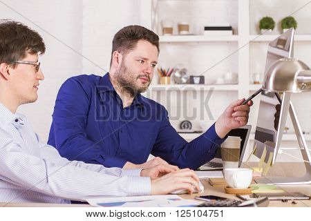 Businessmen in office looking at blank display and discussing something