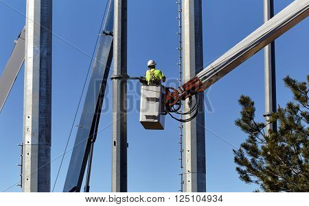 Utility worker in a boom crane basket servicing utility poles