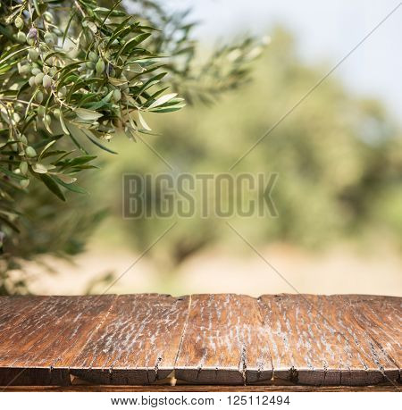 Olives with old wooden table. Blur nature background.