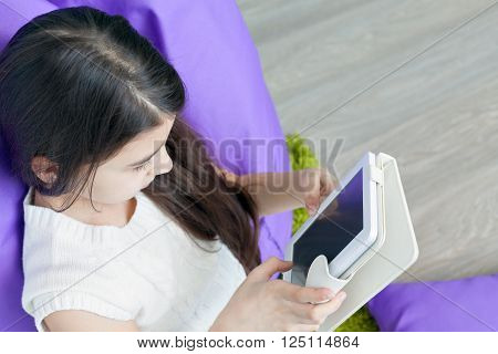 little girl reading e-book in the room. Reading e-books. Education, leisure, technology and the concept of the Internet - a little girl with a tablet PC at home.