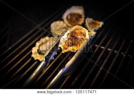 A chef removes oysters cooking on a barbecue grill