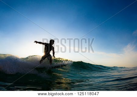 The silhouette of a surfer man riding a short board on a wave