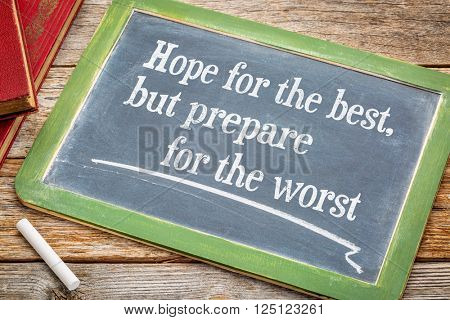 Hope for the best but prepare for the worst - advice on a slate blackboard with a white chalk and a stack of books against rustic wooden table poster