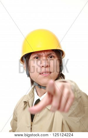 portrait of young Japanese construction worker scolding
