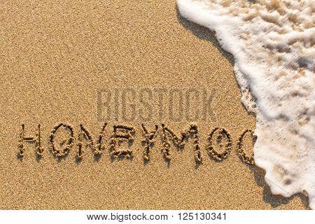 Honeymoon - drawn of the hand on the beach sand, soft surf wave.