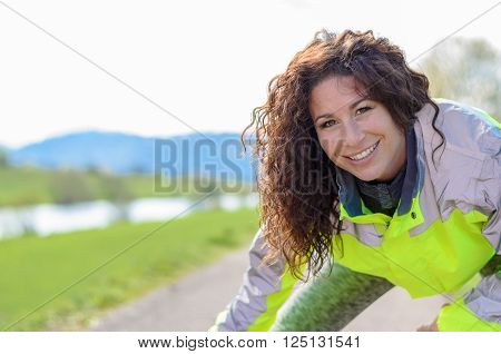 Smiling attractive woman wearing a luminous high visibility jacket working out on a rural road close up of her face