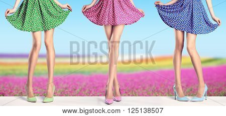 Woman long legs in fashion dress and high heels. Perfect female  sexy legs in stylish colorful skirt and summer glamour shoes on flower field. Unusual creative elegant walking out outfit, people