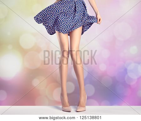 Woman long legs in fashion dress, high heels. Perfect female  sexy legs, stylish purple skirt and summer glamour shoes, colorful abstract background. Unusual creative elegant walking out outfit, people