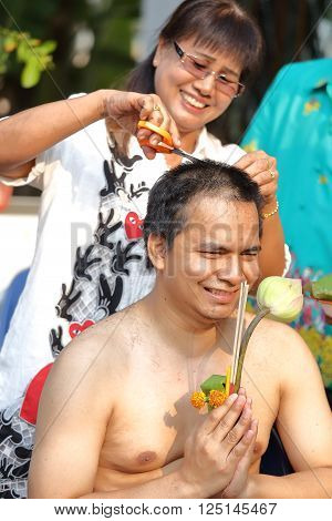 woman cut hair of man for be Ordained to new monk