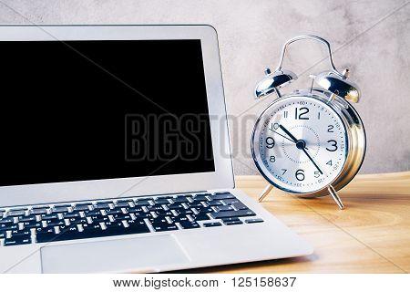 Closeup of black laptop screen and alarm clock on wooden desktop. Mock up
