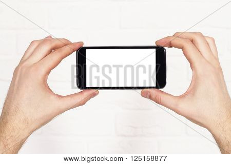 Male hands holding blank white smartphone on white background. Mock up