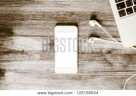Top view of blank white smartphone headphones and keyboard on wooden desktop. Mock up