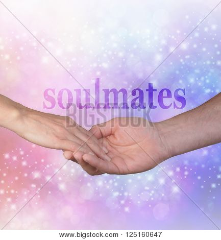 Forever my Soulmate -  Man gently holding female hand with the word SOULMATES above on a sparkling glitter blue and pink bokeh background ideal for engagements, marriage proposals and wedding literature