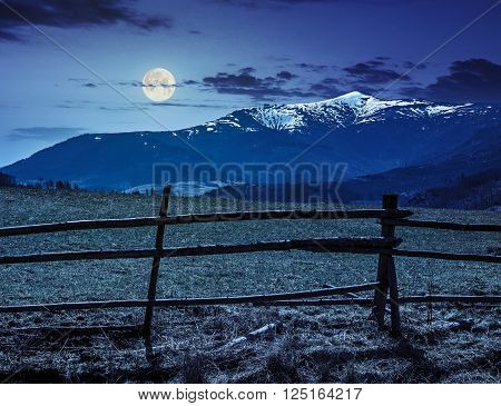 fence on the rural meadow in mountain region in spring time at night in full moon light