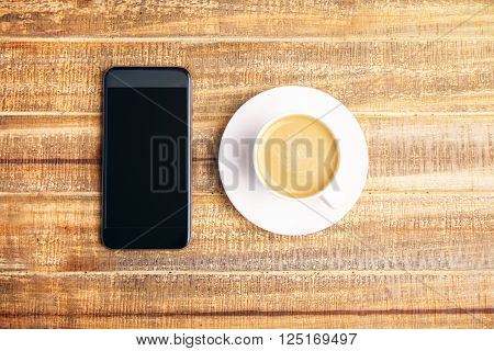 Topview of blank phone and coffee on wooden table. Mock up