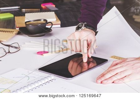 Male hand using tablet placed on large whatman with office tools