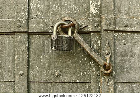 Steel worn padlock with old door heck at the iron textured door. Selective focus at the padlock. Sepia tones filter applied