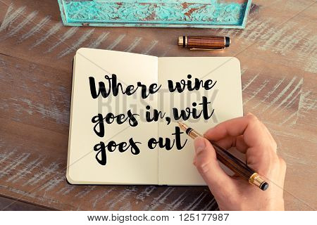 Retro effect and toned image of a woman hand writing on a notebook. Handwritten quote Where wine goes in, wit goes out as inspirational concept image