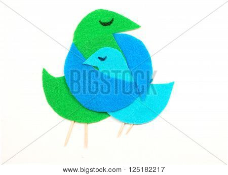Felt cut out bird shapes in green and blue with toothpick legs and black marker eyes. Mom bird is embracing baby bird. Isolated on white.