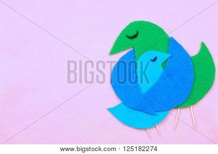 Felt cut out bird shapes in green and blue with toothpick legs and black marker eyes. Mom bird is embracing baby bird. Background is soft pink felt. Copy space