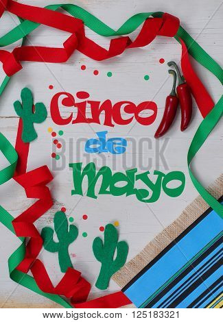 A fun Mexican themed border and message with red and green ribbons wandering in and out of frame decorated with a serape blanket chili peppers cactus shapes cut out of felt and confetti on a rustic wood background