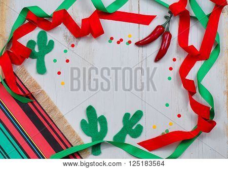A fun Mexican themed border with red and green ribbons wandering in and out of frame decorated with a serape blanket chili peppers cactus shapes cut out of felt and confetti on a rustic wood background. Copy space.