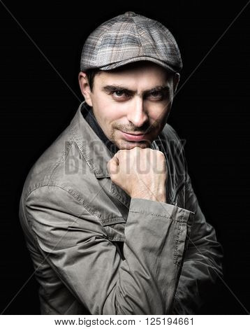Stylish man in the pose of relying on his fist on a black background