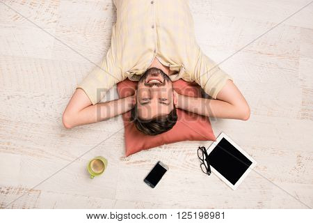 Top view photo of man lying on the floor with cup phone glasses and tablet
