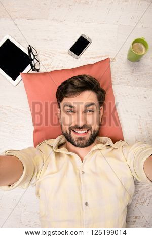 Handsome Man Lying On The Floor On Pillow  And Making Selfie