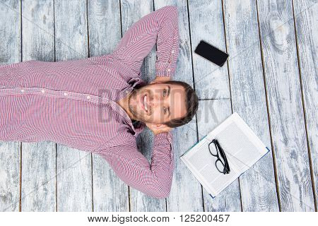 Top view photo of smiling man lying on the floor with book phone and glasses