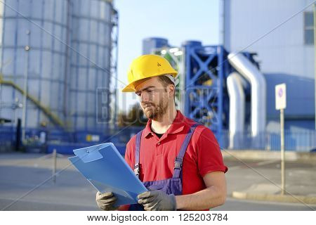 Worker quality control check working outside a modern factory