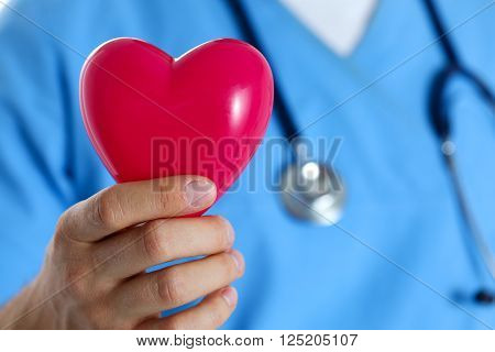 Male Medicine Doctor Wearing Blue Uniform Hold In Hand Red Toy Hear