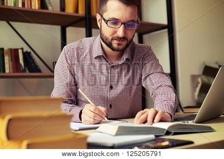 Close up of serious businessman who rewriting from a book and laptop