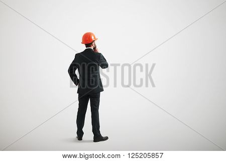 Back view of man standing straight and touching his beard wearing formal wear