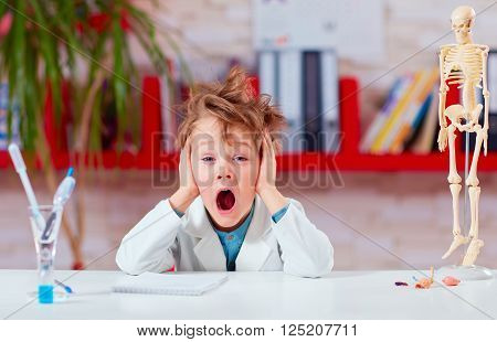 young kid schoolboy yawning during experiment in school lab