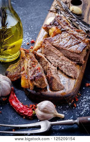 Grilled steak sliced on a cutting board. Entrecote with garlic and chilli on a dark background.