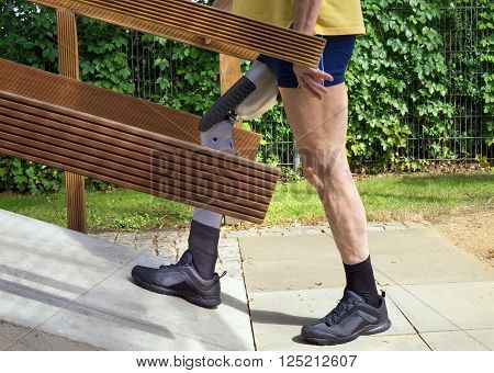 Unidentifiable man walking on ramp with false leg for exercise.  Side view on single unidentifiable man in blue shorts and yellow shirt walking up concrete ramp with prosthetic leg outdoors.